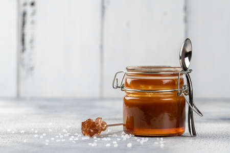 Homemade salted caramel sauce. Selective focus, space for text. On light background