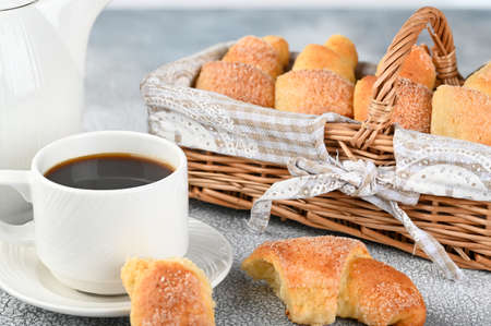 Sweet homemade cottage cheese buns with sugar and coffee cup on light background