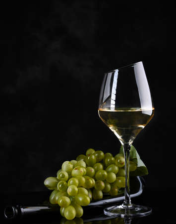 Wine background. White wine in wineglass, grape on old bottle . On the black background.