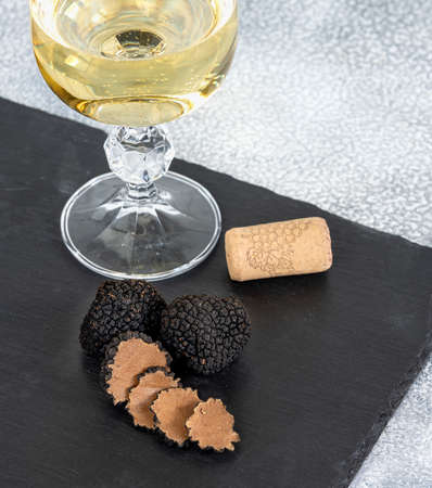 Black truffles and slices with white wine on black stone background.