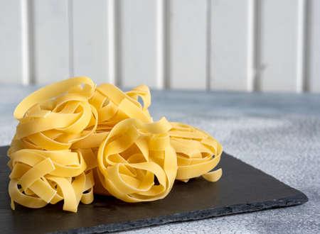 Rolled tagliatelle shape of italian pasta on black stone background. High quality photo