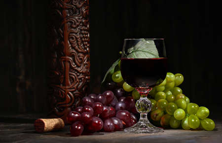 Red wine in glass with vintage bottle and with bunch of red and white grapes on wooden dark background.