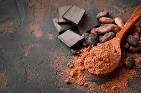 Dark chocolate, red chilli peppers, cocoa beans and powder on a dark stone background, top view, selective focus.