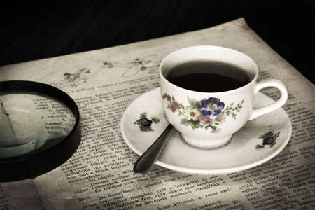 oude krant: Coffee porcelain cup on old newspaper with magnifying glass