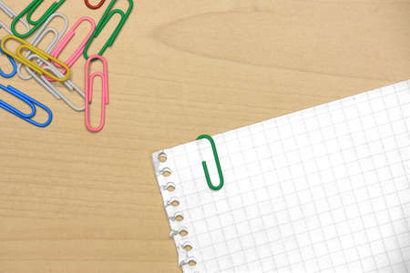 Colorful paper clips on wood with grid papers