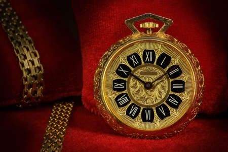 red pillows: Old pocket watch with golden chains on red pillows