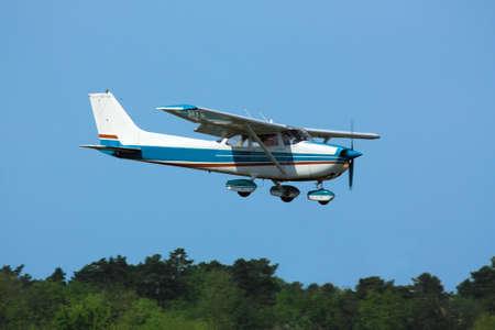 最後の緑の木々 の上に一般航空用軽飛行機