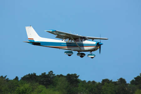 squawk: Light general aviation  plane on final over green trees