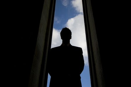 obscured: Business person in a suit silloutted in an tall window. Stock Photo
