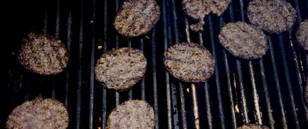 Shot of a bunch of hamburgers on a commercial grill.