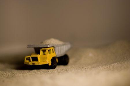 dumptruck: A closeup of a toy dumptruck in sand. Stock Photo