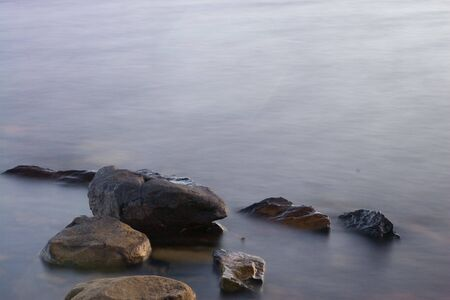 Long exposure of some rocks in a pond at sunset.