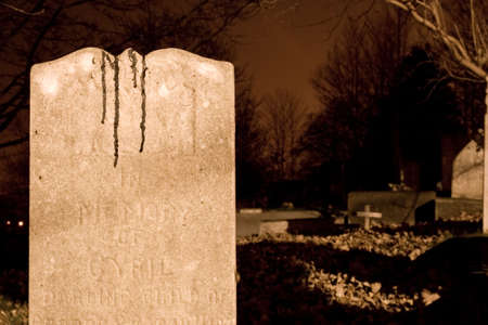 Gravestone in a old graveyard at night. Probably isn't blood, but it sure looks it.