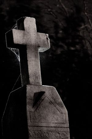A cross on a tombstone, backlight with a hot shoe flash.