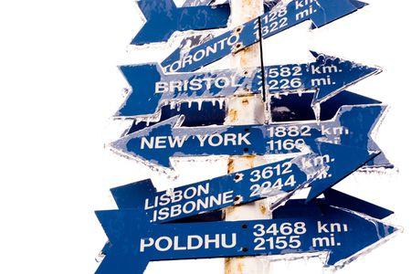 chilometro: Signpost in cima alla collina del segnale, st John, Terranova, Canada indicante alle posizioni chiave intorno al mondo, coperto in neve.