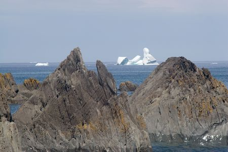 Ragged rocks along the shoreline parralell the peaks of the icebergs floating in the distance off the coast of the Bonavista peninsula, Newfoundland.