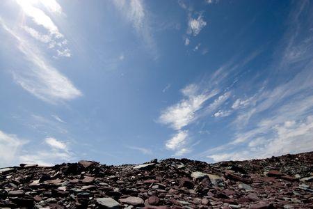 Rocky hill at a slate quarry framed by a blue expansive sky.