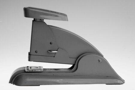 office stapler: Vintage grey stapler on a grey gradient background.