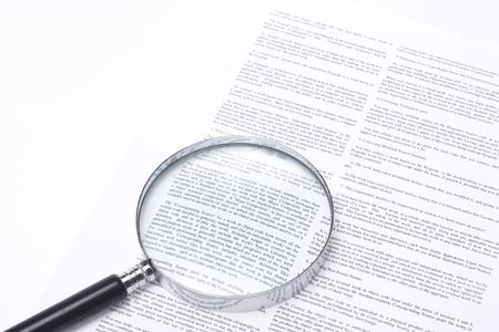 Close up on a legal contract with a magnifying glass