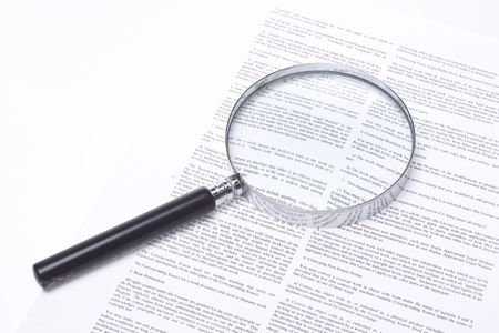 Still life showing a magnifying glass lying on a legal contract.