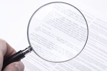 Hand holding a magnifying glass, showing the confusing fine print of a legal contract.