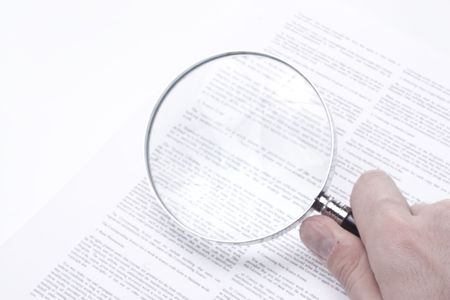 Close up on a legal contract with a hand holding a magnifying glass.