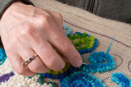 hooking: Detail showing a hand hooking a rug, a traditional maritime craft that recyles old fabrics into vibrant mats using burlap.  Stock Photo