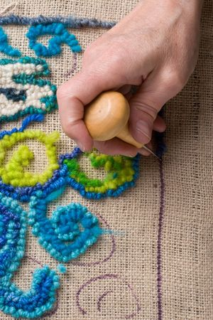 hooking: Hooking a rug, a traditional New England craft that recyles old fabrics into vibrant mats using burlap.  Stock Photo