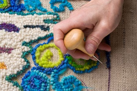 Hooking a rug, a traditional English craft that recyles old fabrics into vibrant mats using burlap.