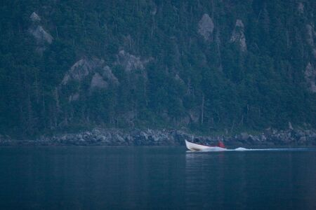 Small boat below majestic mountain at dusk.