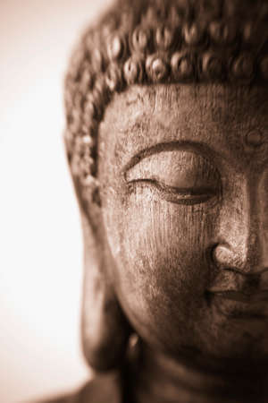 cabeza de buda: Esta es una fotograf�a de primer plano de una talla de madera antigua de una escultura de Buda con el foco en el ojo abatido La imagen fue tomada con una lensbaby y tiene una profundidad de campo muy baja