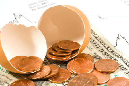 Broken egg with pennies and dollar bills photo
