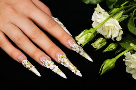 unas largas: El diseño del arte de uñas sobre un fondo negro