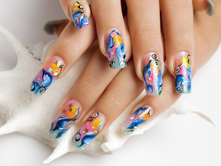 Female hands with sea design be on seashell. photo