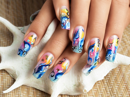 acrylic nails: Female hands with sea design be on seashell.