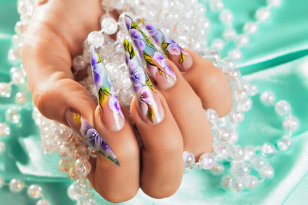 artificial flowers: Female hand with  beautiful floral design on  nails.