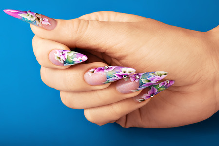 artificial flower: Female hand with  beautiful floral design on  nails.