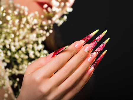 artificial flower: Female hand with beauty pink floral design nails . Stock Photo