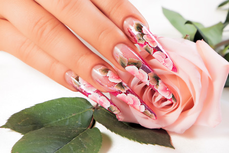 french model: Beauty floral design nails on female hand.