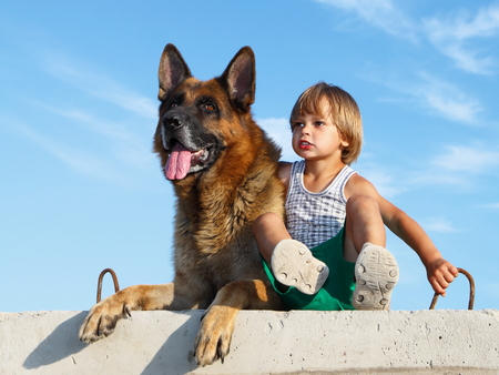 Cute boy and threatening German shepherd looking into distance. Stok Fotoğraf