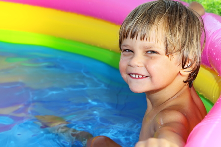 kiddie: Tanned cheerful boy practicing swimming in the pool.