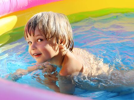 Tanned cheerful boy practicing swimming in the pool.