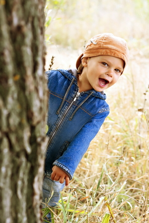 Kid in denim jacket peeping from behind a tree. Stok Fotoğraf