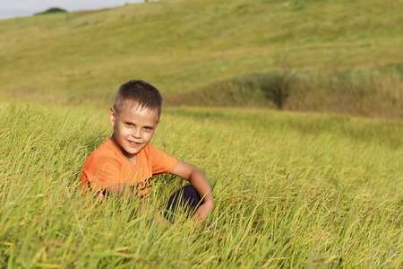 Young boy resting sitting in green grass.
