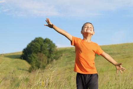 Joven del juego de niño feliz en concepto meadow.Freedom.