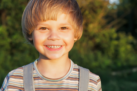 Portrait  adorable young boy at sunset in nature.