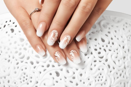 Manicure and white abstract pattern on womens nails