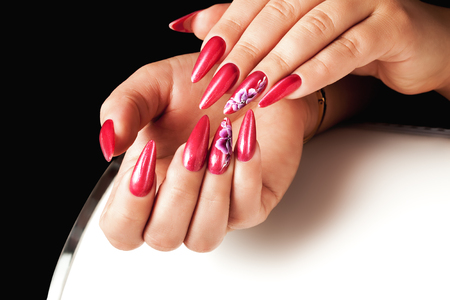 Acrilyc red nails on hands and floral deign.