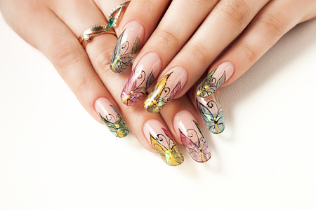 Summer female manicure with a butterfly pattern.