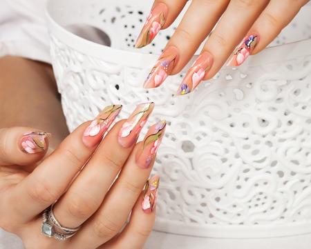 Weibliche Hand mit floralen Kunst Design Nägel. Standard-Bild - 77222893